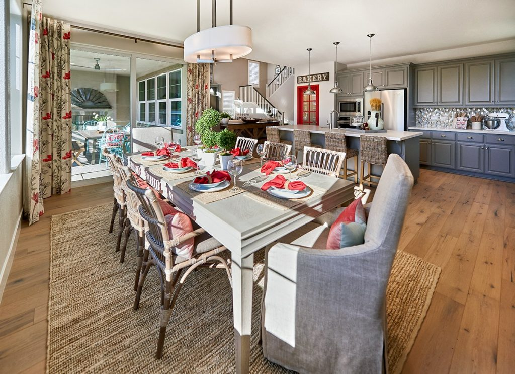 Dining room with off-white traditional dining table, wicker chairs and jute natural area rug, oval fabric and chrome chandelier, floral curtains, slider door, light brown wood flooring