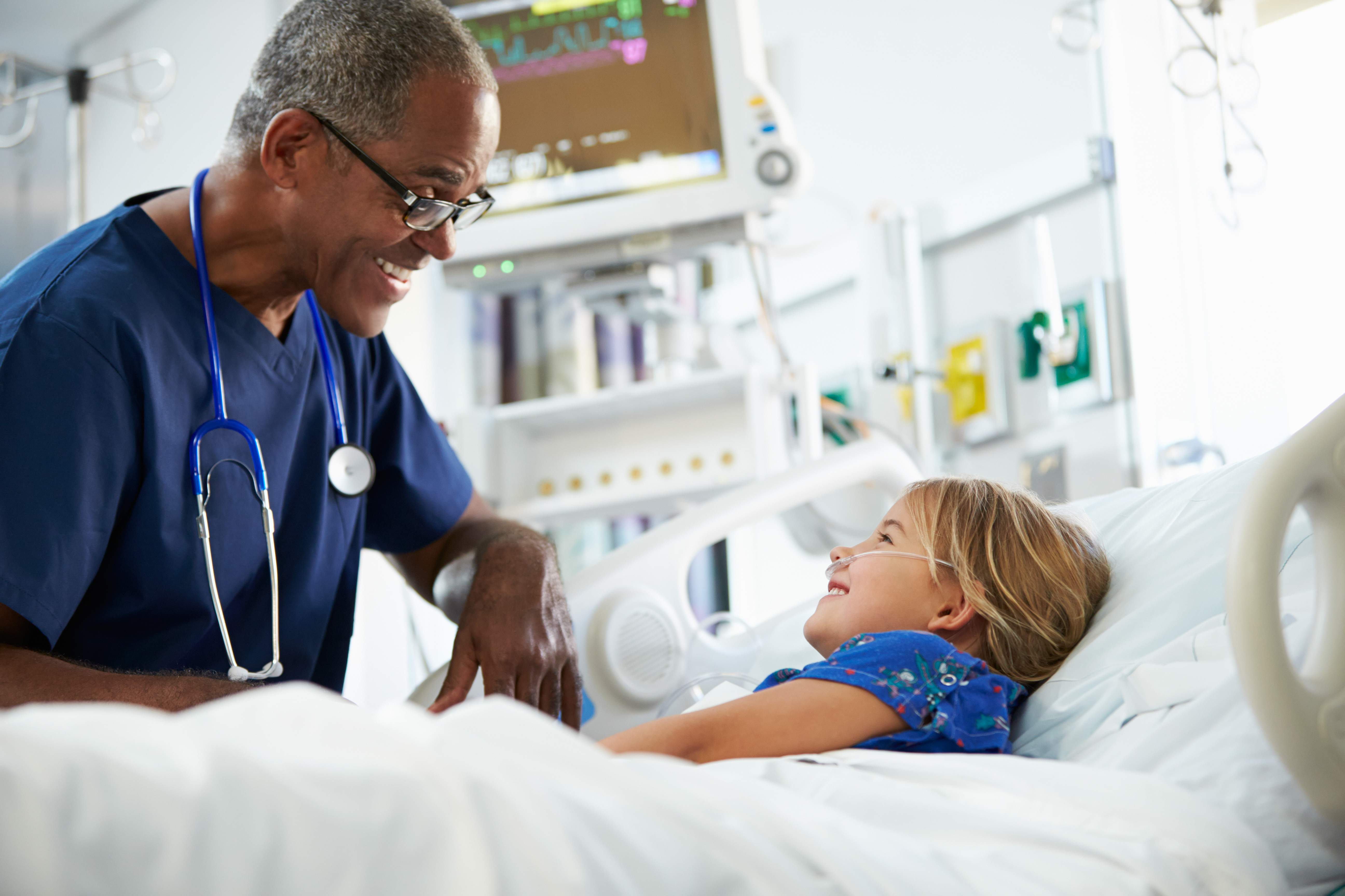 Male nurse talking to child in hospital bed